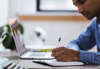 mann schreibt mit stift auf notizbuch lapotp im hintergrund