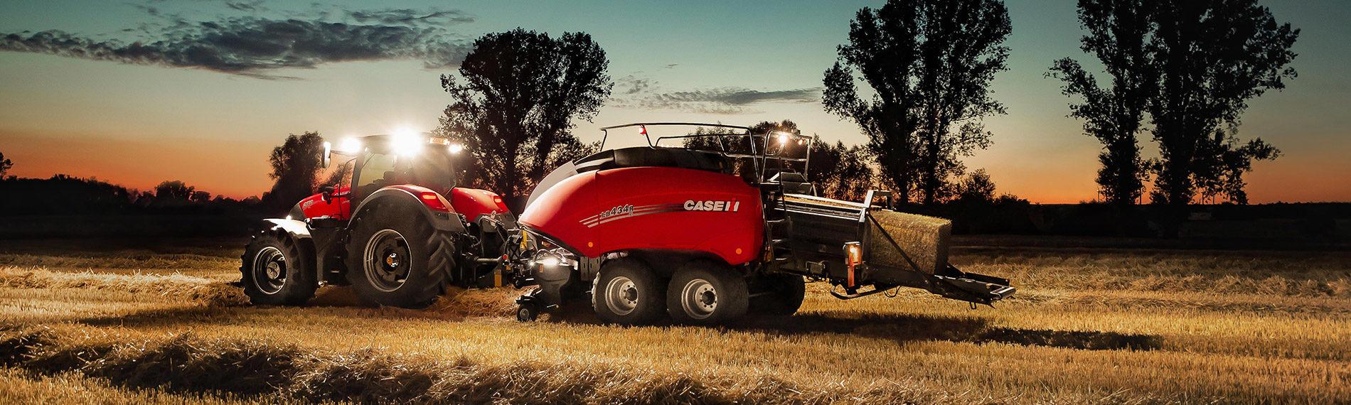 case traktor mit grossballenpresse bei nacht