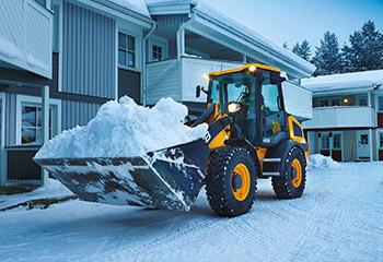 gelber radlader jcb mit schnee in schaufel
