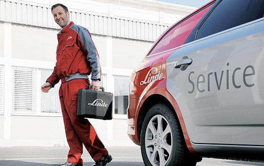 servicetechniker vor gruma firmenwagen mit koffer in der hand