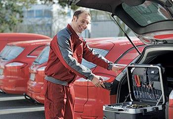 servicetechniker vor gruma firmenwagen mit werkzeugkoffer