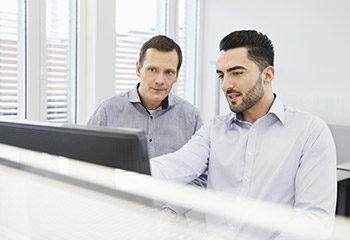 vorschaubild verkaeufer erklaert kunden etwas am computer