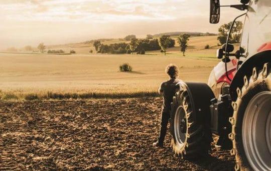 kind steht vor feld neben traktor sonnenuntergang